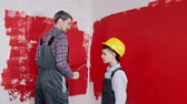 muren : A little boy and his father painting walls - hugging and smiling
