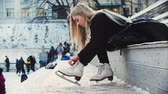 kunstschaatsen : A young woman with blond hair tie up her figure skates before walking out on the rink
