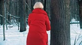 scii : A woman in red down jacket takes ski near the tree and going forward Filmati Stock