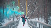 Two young happy women running on the snowy bridge holding smoke bombs