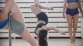 Women on pole dancing training in the bright fitness studio