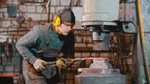 Forging industry - a man blacksmith putting the hot piece of metal under the pressure of big machine - making a knife