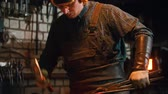 Blacksmith working in the workshop - man worker hitting the piece of metal with a hammer Wideo