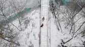 Two colorful young women running on the snowy bridge and having fun with each other