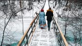 Two young women drinking hot drinks from the bottle and walk on the snowy bridge