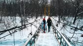 Two young women drinking hot drinks and walk on the bridge Wideo