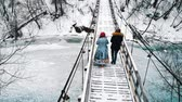 Two young women friends drinking hot drinks from the bottle on the bridge in winter forest