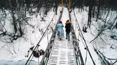 Two women friends drinking hot drinks from the bottle on the snowy bridge in winter forest