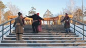 putperest : Russian folk - people in traditional Russian clothes are dancing on the stairs in winter