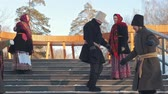 tradiční kultura : Russian folk - men and women in traditional Russian clothes are dancing on the stairs in winter