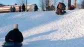 tradiční kultura : Russian folk - men and women in Russian folk costumes are riding a snow slide