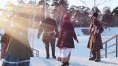 putperest : Russian folk - women in bright scarves are dancing with men on the stairs in the winter park