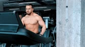 omuz : A bearded attractive young man bodybuilder running on the treadmill with an effort in the modern gym Stok Video