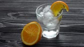 Adding ice cubes in glass with slices of citrus and rosemary on dark wooden table. Cooking process