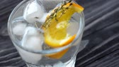 Close-up of a cocktail in a glass with ice, a piece of orange and a sprig of rosemary. Macro view with slow refocusing. Cocktail with citrus fruits on dark wooden table