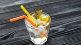 Beverage with ice, decorated with an orange slice and rosemary top view. Two straws in glass. Fresh cocktail on dark wooden table