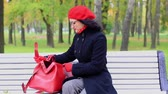 сюрприз : Woman looking something in red bag, on bench in autumn park. teachers day