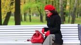 сюрприз : Woman with red bag in autumn park.