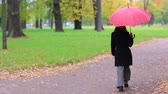 boina : Woman with red umbrella in the autumn park. Archivo de Video