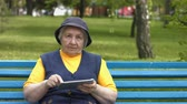 without internet : Grandmother uses a tablet computer. An elderly woman sits on a bench in the park. Stock Footage