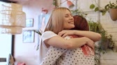 expressando positividade : Two young beautiful girls friends meet and embrace in a cafe. Friendly and love relationship.