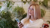 gesticulation : Young beautiful woman blonde in glasses dancing to the music from a smartphone at a cafe table. Rest and good mood.