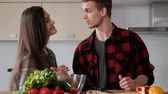 casamento : Young beautiful couple in plaid shirts are cooking at home in the kitchen. A woman and a man cut vegetables and make a salad of pepper, tomato, radish in a transparent glass dish. Two glasses of wine.