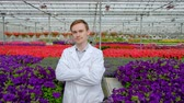 analyzing : Young male scientist or agronomist in a white coat against the background of the beds with flowers in the greenhouse. Looking at the camera and showing thumbs up.