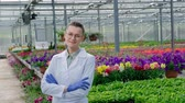 analyzing : Young beautiful middle-aged woman in glasses, white coat and blue rubber gloves, scientist agronomist, posing against greenhouse with green plants and flowers. Smiles and looks straight into camera.