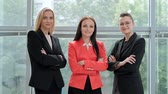 Three young attractive women in business suits posing against the backdrop of a light office. Head and subordinates. Working team of professionals and colleagues. Feminism and feminine power.