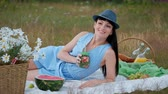 A young beautiful woman in a hat and dress is drinking lemonade from a can while sitting on a plaid on the green grass. Picnic basket, a bouquet of daisies, watermelon. The concept of giving away in nature.
