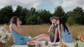 Three young attractive girls on a picnic. The photographer takes pictures on the mirrorless camera of two models. Models pose and watch photos. The concept of outdoor recreation. Vídeos