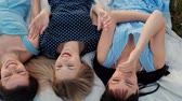 Three young attractive women are lying on a plaid and looking at the sky. Laugh and point up, dance. Rest girlfriends outdoors nature. Picnic concept. Vídeos