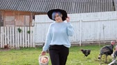 volaille : Young beautiful woman farmer in a sweater and a black hat with a brim against a background of green grass and a coonhouse. Holds a basket of chicken eggs.