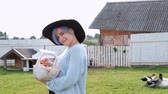 galinha : Young beautiful woman farmer in a sweater and a black hat with a brim against a background of green grass and a coonhouse. Holds a basket of chicken eggs.