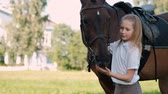psicologia : Girl teenager walks on the field with a brown horse. Hugs and feeds her apples.