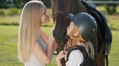 jokey : Mother and daughter riders and jockeys on a green field hugs and kisses a brown horse. Mentor and student. Stok Video