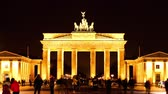 emberek : Timelapse of Tourists pass by in front of the famous Brandenburger Gate at night on January 26, 2015 in Berlin, Germany.
