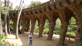 mimar : BARCELONA, SPAIN – JULY 11: View on the Park Guell as Visitors pass by on July 11, 2016 in Barcelona, Spain. Stok Video