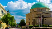 римский : PECS, HUNGARY - AUGUST 15: Time-lapse view on the Downtown Candlemas Church of the Blessed Virgin Mary Church as pedestrians pass by on August 15, 2018 in Pecs, Hungary