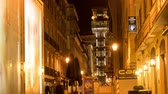 булыжник : LISBON, PORTUGAL - CIRCA JANUARY 2018: Time-lapse view of illuminated streets in the historic centre of the city as people and traffic pass by at night circa January 2018 in Lisbon, Portugal.
