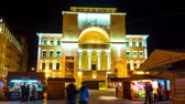 piata : TIMISOARA, ROMANIA - OCTOBER 15: Time - lapse view on people as they pass by at the traditional market front of historical building of the Romanian National Opera at night on October 15, 2017 in Timisoara, Romania.