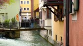 декорации : AUGSBURG, GERMANY - APRIL 15: View on streaming water in the canal  between historical houses as peolple pass by on a bridge in the centre of the city on April 15, 2017 in Augsburg, Germany. Стоковые видеозаписи