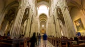 potřísněný : MADRID, SPAIN - CIRCA MARCH 2017: Time-lapse view on the architecture of a catholic church interior as peope pass by between pews circa March 2017 in Madrid, Spain. Dostupné videozáznamy