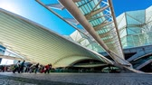 lisboa : LISBON, PORTUGAL - CIRCA JANUARY 2018: Time-lapse view on the contemporary architecture of  Lisbon Oriente Railway Station as people pass by on a sunny day circa January 2018 in Lisbon, Portugal.