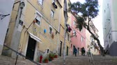 godo : LISBON, PORTUGAL - CIRCA JANUARY 2018: View on daily life as people pass by on a cobblestone street in the famous Alfama district circa January 2018 in Lisbon, Portugal.