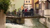 riverside : AUGSBURG, GERMANY - APRIL 15: View on streaming water in the canal  between historical houses as peolple pass by on a bridge in the centre of the city on April 15, 2017 in Augsburg, Germany. Stock Footage