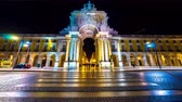 monumentální : LISBON, PORTUGAL - CIRCA JANUARY 2018: Time-lapse view of the illuminated City Gate in the historic centre of the city as people and traffic pass by at night circa January 2018 in Lisbon, Portugal.