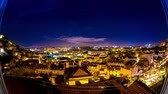 tetőtéri : Panoramic night time-lapse view of fast moving clouds over the illuminated buildings of the city and the iconic 25th of April bridge in Lisbon.