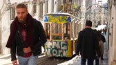 místní : LISBON, PORTUGAL - CIRCA JANUARY 2018: View on a typical old tram wait for passangers on the top of a steep street as people pass by in the old town circa January 2018 in Lisbon, Portugal. Dostupné videozáznamy